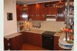 Большая кухня сложной формы с древесными глянцевыми фасадами